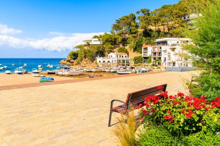 Flowers and bench on coastal promenade and view of fishing boats on beach in beautiful Sa Riera village, Costa Brava, Catalonia, Spain Фото со стока - 130816049