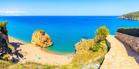 Panorama of Cala Moreta beach with famous Isla Roja rock in blue sea and walking path on side, Costa Brava, Catalonia, Spain