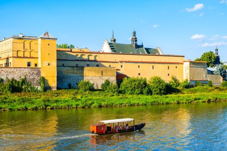 Tourist boat sailing on Vistula river with old church buildings in background, Krakow, Poland