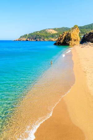 Unidentified young woman standing on Cala Moreta beach and looking at blue sea, Costa Brava, Catalonia, Spain