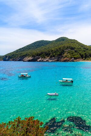 Fishing boats on azure sea water in beautiful bay of Cala Sant Vicent, Ibiza island, Spain