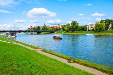 KRAKOW, POLAND - SEP 8, 2019; Tourist boat sailing on Vistula river with Wawel castle in background, Poland. Stock fotó
