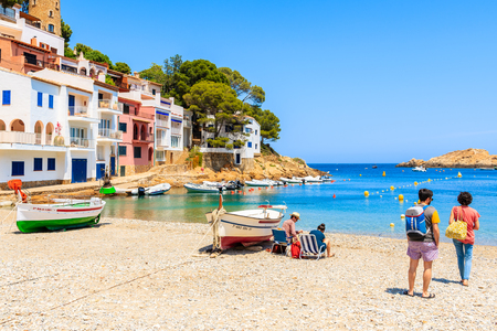 SA TUNA BEACH, COSTA BRAVA - JUN 7, 2019: Couple of backpackers walking on beach in Sa Tuna village with colorful houses on shore, Costa Brava, Catalonia, Spain
