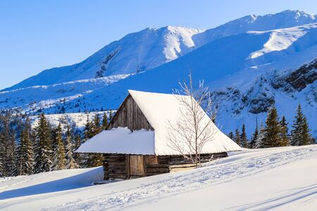 Old wooden mountain hut in beautiful winter landscape of Gasienicowa valley after fresh snowfall, Tatra Mountains, Poland