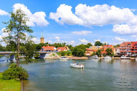 Yacht sailing on canal in Mikolajki town on sunny summer day, Mazury Lake District, Poland