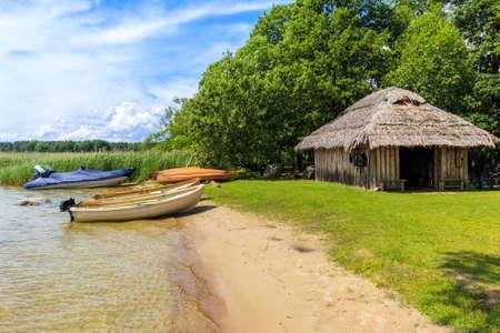 Fishing boats on small sandy beach of Beldany Lake near Iznota village, Mazury Lake District, Poland