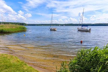 Small beach at Nidzkie lake and sailboats in distance near Ruciane Nida town, Mazury Lake District, Poland