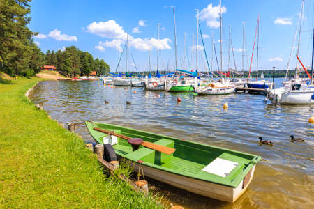 Fishing boat and sailing boats along pier on lake shore in Krzyze village port on sunny summer day, Mazury Lake District, Poland