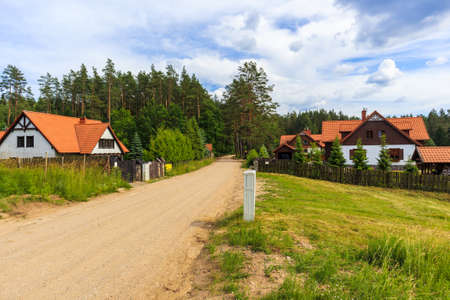 Rural road and traditional style rustic houses in Wygryny village near lake Nidzkie, Mazury Lake District, Poland