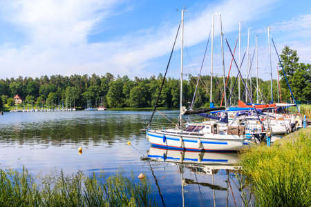 Sailboats reflection in lake Nidzkie near Ruciane Nida town, Mazury Lake District, Poland