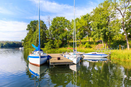 Sailing boats on lake shore in Ruciane-Nida town marina in early morning sunlight, Mazury Lake District, Poland