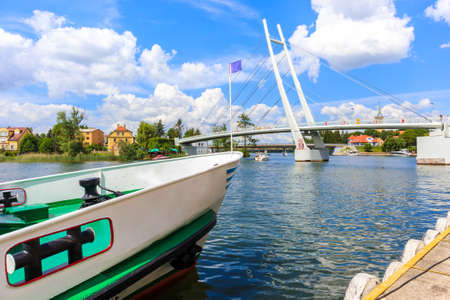 Boat mooring in Mikolajki port with bridge in background on sunny summer day, Mazury Lake District, Poland