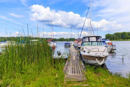Boats on lake shore in Wygryny village marina, Mazury Lake District, Poland Zdjęcie Seryjne