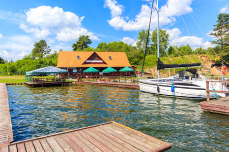 Sailing boats and restaurant on lake shore in Krzyze village port on sunny summer day, Mazury Lake District, Poland