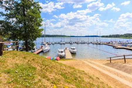 Sailing boats on lake shore in Krzyze village port on sunny summer day, Mazury Lake District, Poland Zdjęcie Seryjne