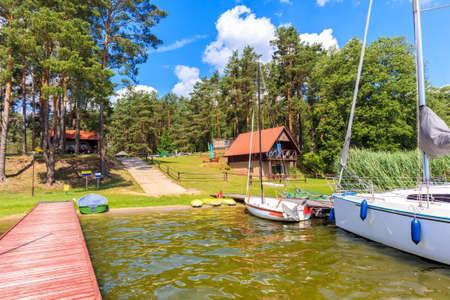 Sailing boats and summer house on lake shore in Krzyze village port on sunny day, Mazury Lake District, Poland