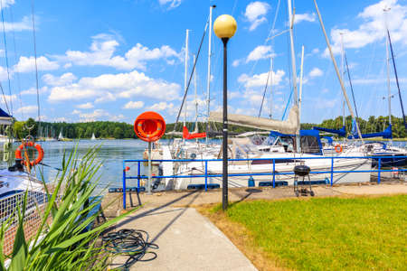 Sailing boats anchoring at pier on Lake Beldany in port Wierzba on summer sunny day, Mazury Lake District, Poland