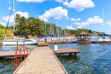 Sailing boats and pier on lake shore in Krzyze village port on sunny summer day, Mazury Lake District, Poland