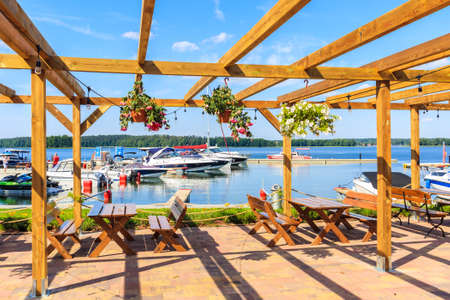 Restaurant tables on terrace with flowers and view of sailing boats on lake Beldany in Piaski port on summer sunny day, Mazury Lake District, Poland