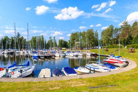 Sailing boats on lake Beldany in Piaski port on summer sunny day, Mazury Lake District, Poland