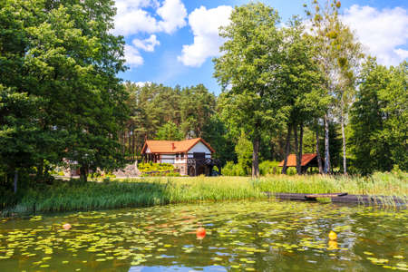 Summer house on lake shore in Krzyze village port on sunny day, Mazury Lake District, Poland