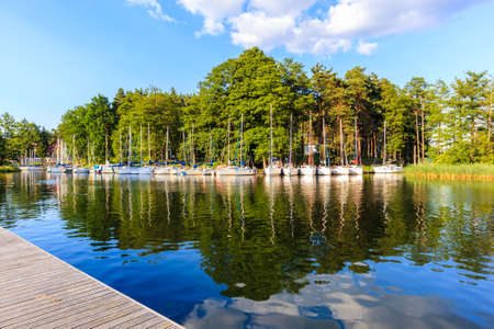 Reflections of sailing boats on lake shore in Ruciane-Nida town marina at sunset time, Mazury Lake District, Poland