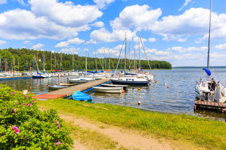 Sailing boats and pier on lake shore in Karwica village port on sunny summer day, Mazury Lake District, Poland Zdjęcie Seryjne