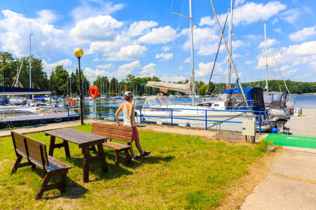 Young female tourist standing near sailing boats at Lake Beldany in port Wierzba on summer sunny day, Mazury Lake District, Poland