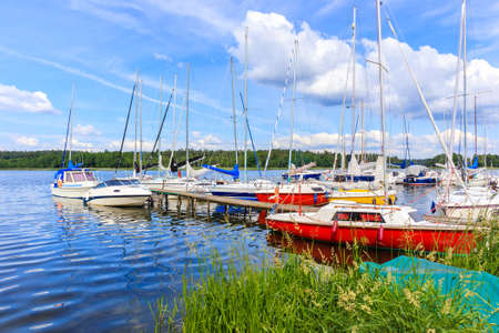 Sailing boats on lake shore in Wygryny village marina, Mazury Lake District, Poland