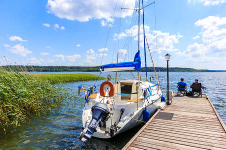 Two unidentified men fishing on pier and sailing boat mooring on lake shore in Krzyze village port on sunny summer day, Mazury Lake District, Poland Zdjęcie Seryjne