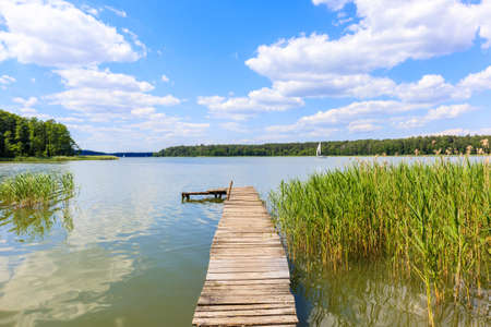 Wooden pier and grass on lake Nidzkie shore on sunny summer day with beautiful clouds on blue sky, Mazury Lake District, Poland Zdjęcie Seryjne