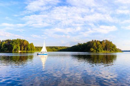 Sailing boat on lake Nidzkie in Ruciane-Nida at sunset time, Mazury Lake District, Poland