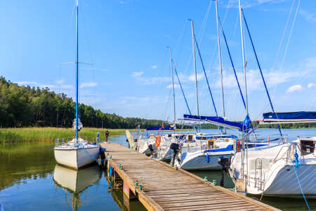 Sailing boats at pier on lake Beldany in Piaski port on summer sunny day, Mazury Lake District, Poland