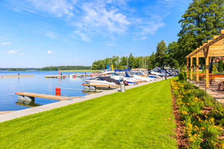 Restaurant with flowers on green lawn and view of sailing boats on lake Beldany in Piaski port on summer sunny day, Mazury Lake District, Poland Zdjęcie Seryjne
