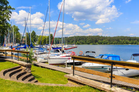Sailing boats anchoring at pier of Lake Beldany in port Wierzba on summer sunny day, Mazury Lake District, Poland Zdjęcie Seryjne