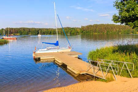 Sailing boat anchoring at pier on lake Nidzkie in Ruciane-Nida public beach at sunset time, Mazury Lake District, Poland