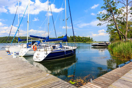 Sailing boats anchoring at pier of Lake Beldany in port Wierzba on summer sunny day, Mazury Lake District, Poland
