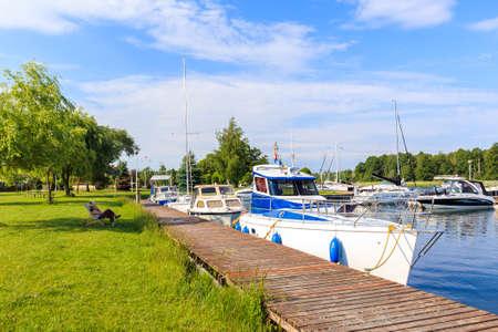 Boats anchoring at pier in Pisz sailing port on Lake Ros on summer sunny day, Masurian Lakes, Poland