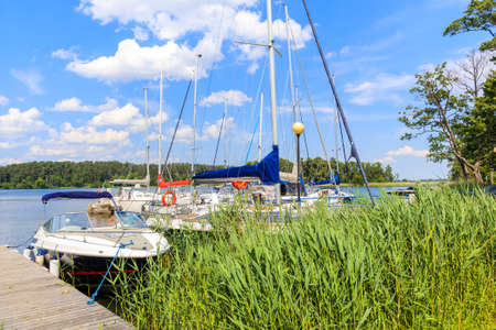 Sailing boats anchoring at shore of Lake Beldany in port Wierzba on summer sunny day, Mazury Lake District, Poland