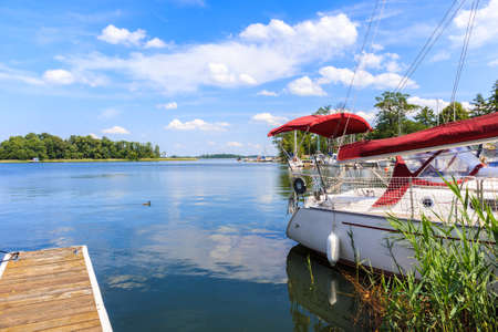 Sailing boat anchoring at shore of Lake Beldany in port Wierzba on summer sunny day, Mazury Lake District, Poland