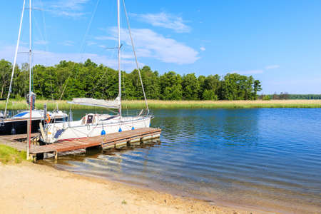 Beach in Pisz sailing port on Lake Ros on summer sunny day with yacht boat at pier in background, Masurian Lakes, Poland
