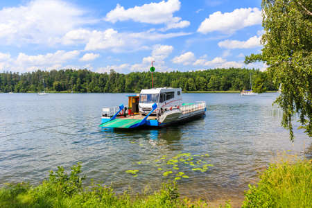 Ferry transporting camper car to Wierzba sailing port on Lake Beldany on summer sunny day, Masurian Lakes, Poland.