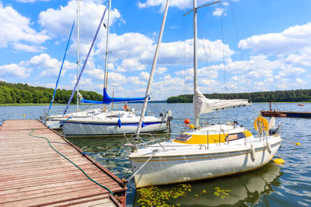 Sailing boats and pier on lake shore in Karwica village port on sunny summer day with with clouds on blue sky, Mazury Lake District, Poland