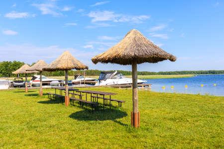 Beach umbrellas on green lawn in Pisz sailing port on Lake Ros on summer sunny,  Masurian Lakes, Poland