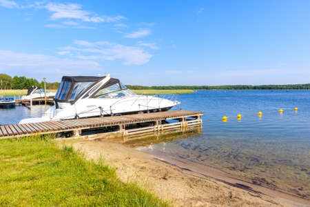 Boats anchoring at beach in Pisz sailing port on Lake Ros on summer sunny day, Masurian Lakes, Poland