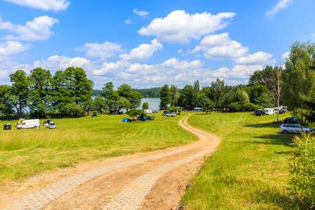 Road to camping site at lake Mokre near Zgon village on summer sunny day, Masurian Lakes, Poland