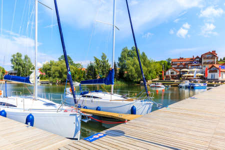 Yacht boats at pier in sailing port Nowe Guty on Lake Sniardwy on summer sunny day, Masurian Lakes, Poland