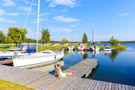 Young woman sitting on pier and looking at boats anchoring in Pisz sailing port on Lake Ros on summer sunny day, Masurian Lakes, Poland