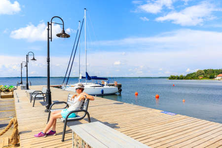 Young woman sitting on pier and looking at boats anchoring in sailing port Nowe Guty on Lake Sniardwy on summer sunny day, Masurian Lakes, Poland