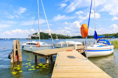 Boats anchoring at pier in Wierzba sailing port on Lake Beldany on summer sunny day, Masurian Lakes, Poland